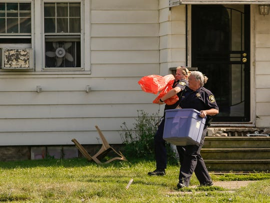 Ingham County Animal Control officers leave a house