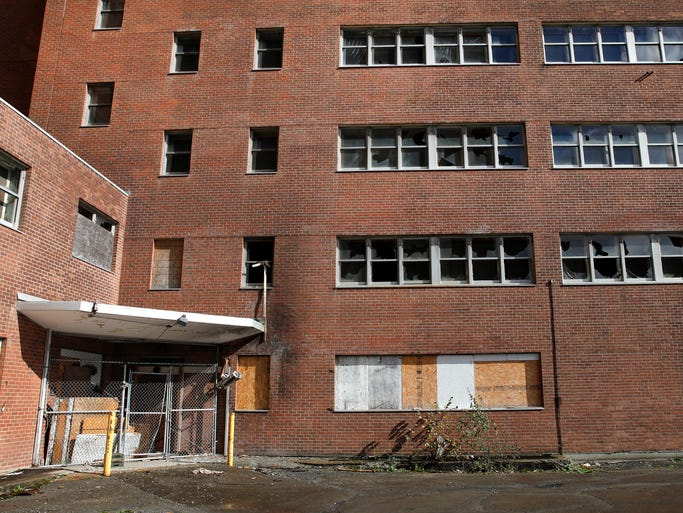 There are many broken and boarded up windows and entrances at the long empty Terrence Building on Elmwood Avenue in Brighton. It is an old psychiatric hospital.