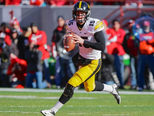 FILE - In this Nov. 29, 2013, file photo, Iowa quarterback Jake Rudock rolls out in the first half of an NCAA college football game against Nebraska in Lincoln, Neb. Iowa could rest largely on the shoulders of junior quarterback Rudock in the 2014 season and an offense that too often stalled against elite competition. (AP Photo/Nati Harnik, File)