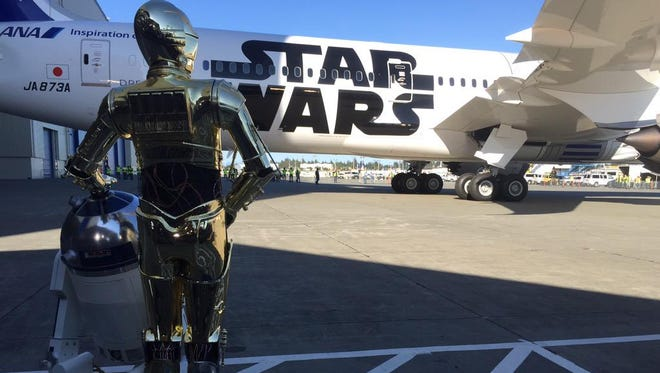 R2-D2 – joined by companion C3PO – watches as a Dreamliner painted in his likeness emerges from a Boeing hangar in Everett, Wash., on Sept. 12, 2015.