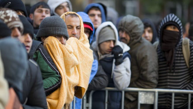 Migrants try to keep warm during temperatures around freezing as they wait for registration and allocation of a sleeping place on the premises of the State Office of Health and Welfare (LaGeSo) in Berlin on Oct. 12, 2015.