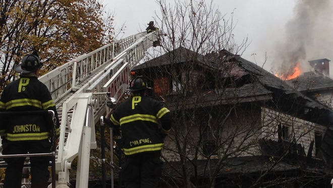 In this Nov. 1, 2014, file photo, Firefighters work to douse a fire that killed six residents in Portland, Maine.