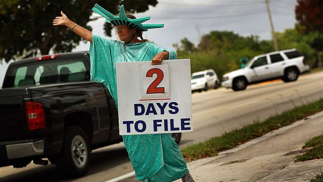 A worker holds a sign advertising a tax preparation office for people that still need help completing their taxes.