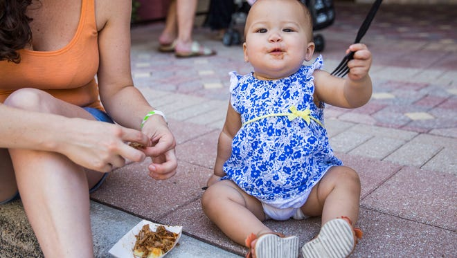 Hollie Rice feeds her daughter Caroline, 1, a pork belly slider during the 34th annual Taste of Collier at Bayfront Place on Sunday, May 6, 2018.