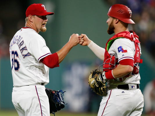 Texas Rangers relief pitcher Austin Bibens-Dirkx and catcher Jonathan Lucroy celebrate the team's 9-3 win win over the Philadelphia Phillies in a baseball game, Wednesday, May 17, 2017, in Arlington, Texas. Bibens-Dirkx made his major league debut. (AP Photo/Jim Cowsert)