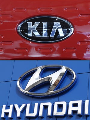 This combination of file photos shows the logo of Kia Motors during an unveiling ceremony on Dec. 13, 2017, in Seoul, South Korea, top, and a Hyundai logo on the side of a showroom on April 15, 2018, in the south Denver suburb of Littleton, Colo., bottom. The Korean automakers are recalling over 591,000 vehicles in the U.S. to fix a brake fluid leak that could cause engine fires.