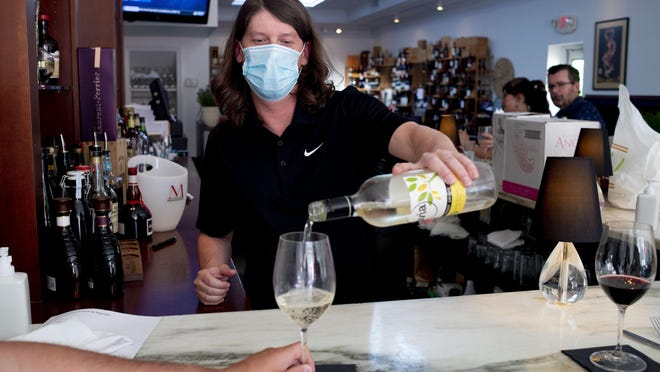 Bartender Brian Barnett wears a mask as he pours a glass of wine for a customer at Cork on Saginaw, which reopened fully for the first time amidst COVID-19 on Monday. Gov. Gretchen Whitmer allowed restaurants statewide throughout Michigan to reopen since the stay-in-place order was issued on March 23. Restaurants in Michigan were closed on March 16. [Jake May | MLive.com] Jake May | Mlive.com