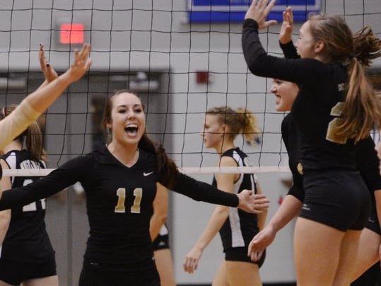 Delone Catholic's Cheyenne Altland, second from left, opens her arms to hug her teammates after defeating South Western during the YAIAA girls' volleyball championship match last year at Dallastown Area High School. Atland will return, as the Squirettes attempt to defend their YAIAA crown. (DAILY RECORD/SUNDAY NEWS -- KATE PENN)