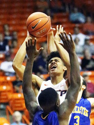 UTEP freshman guard Tim Cameron muscles his way to a layup attempt against Anton Cook, 12, and Gianpalo Riccio, 3, of Southeastern Oklahoma State Sunday at the Don Haskins Center.