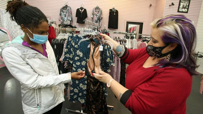 Ashleigh Robinson checks out a dress shown to her by owner Marie Dabbs-Laughlin at her store Midnight Moon Boutique Thursday morning, Nov. 19, 2020, at Eastridge Mall on North New Hope Road.