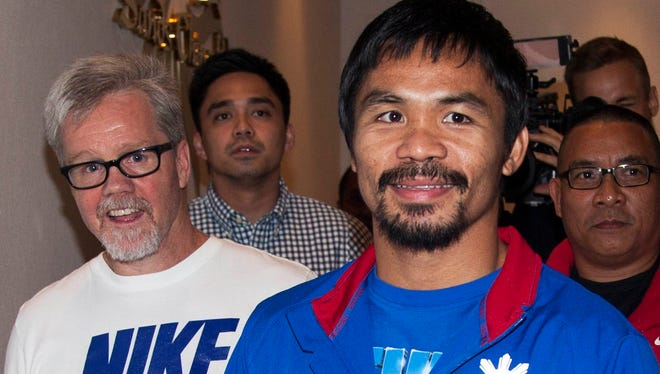 Boxer Manny Pacquiao and his trainer, Freddie Roach, left, arrive at the Venetian Macao hotel in Macau Nov. 19. Pacquiao had a lawsuit against him dismissed in the U.S. on Wednesday