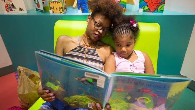Krystal Washington, of downtown, and her daughter, McKenzie Williams, 5, read a book together in The Children's Learning Center in the Hamilton County Public Library in downtown Cincinnati. Washington said her daughter loves books and they often visit the library. The children's area is housed in the annex building of the library, which was built in 1997. The library has signed an agreement with 3CDC to explore the possibility of the non-profit taking over the annex building. All services would in that building would move to the main library.