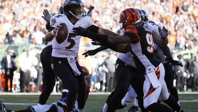 Bengals defensive end Carlos Dunlap puts pressure on Ravens quarterback Joe Flacco in October of 2014 at Paul Brown Stadium.