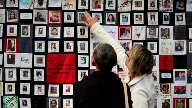 Robin Schuler, left, and Debbie Solberg look at one of three quilts on display Sunday during the Fox Cities Lights of Hope gathering at Appleton's City Park.