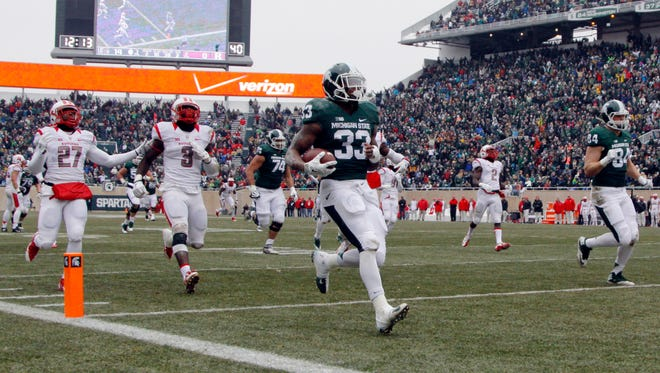 Michigan State's Jeremy Langford scores a touchdown on a 38-yard run in front of Rutgers' Delon Stephenson (27) and Steve Longa (3) during the second quarter Saturday in East Lansing.