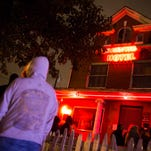 People wait outside in a light rain to walk through the Haunted Hotel.