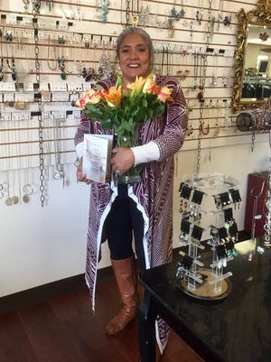Priscilla Potter, owner of Priscilla's Boutique, poses for a photo with flowers on Bosses Day in 2017.