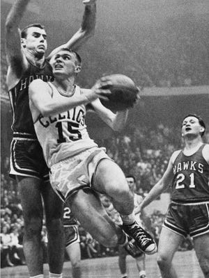 In this April 10, 1958, file photo, Tommy Heinsohn, (15) of the Boston Celtics drives against Bob Pettit, left, of the St. Louis Hawks in their National Basketball Association playoff game at Boston Garden in Boston.  Heinsohn, who as a Boston Celtics player, coach and broadcaster was with the team for all 17 of its NBA championships, has died. He was 86.