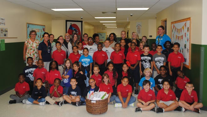 Students in Ms. Hughes's second grade, Ms Paquette's fourth grade and staff members, including Principal Christiana Coburn, present letter and cards the students wrote to thank military men and women overseas to the program organizer, Sharon Tufarelli and Marcie Shatters with Sun Communities Ocean Breeze Resort in Jensen Beach.