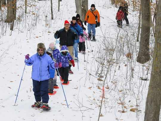 A group of snowshoers hiked through the woods of Lake Maria State Park in 2013.