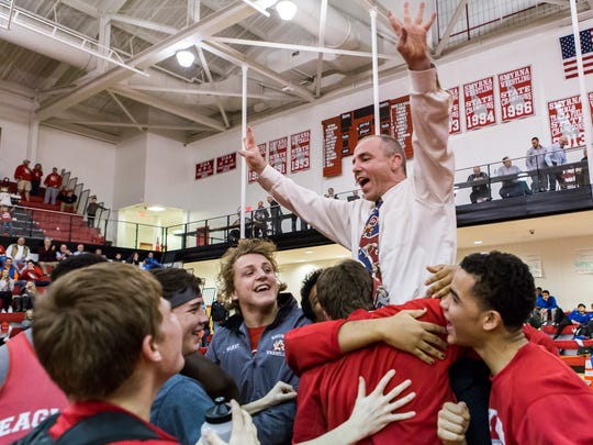 Smyrna players hoist head coach Kurt Howell into the air after winning the DIAA Division I Team Wrestling State Championship at Smyrna High School in 2016.