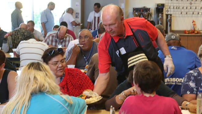 Volunteer Don Waldbeauer serves a Thanksgiving meal to a guest at the Coachella Valley Rescue Mission in Indio, November 23, 2017.