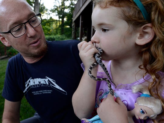"""Mark watches his daughter Maggie kiss her corn snake named """"Zippy"""" while playing around outside Tuesday, June 7, 2016, in Pegram, Tenn. Joanna Montgomery, Mark's wife, died from cancer at the age of 47."""