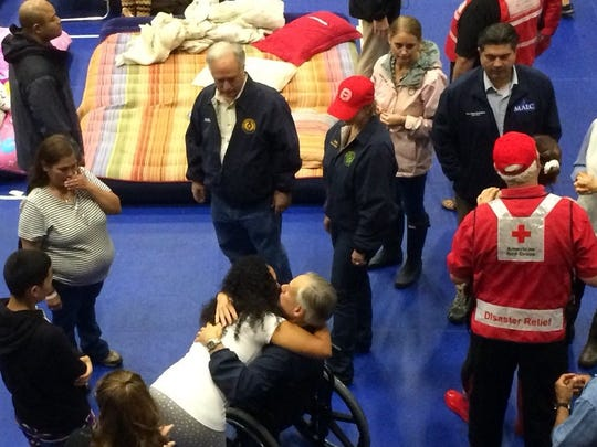 Gov. Greg Abbott hugs Harvey evacuee Shirelle Franklin at an Austin community center.