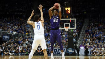 Kansas State Wildcats forward Xavier Sneed rises to shoot against Kentucky Wildcats guard Quade Green.