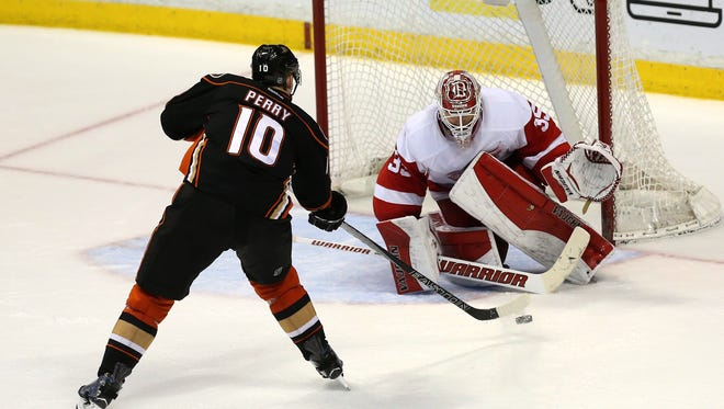 Corey Perry of the Ducks shoots and scores in the shootout against goalie Jimmy Howard of the Red Wings.