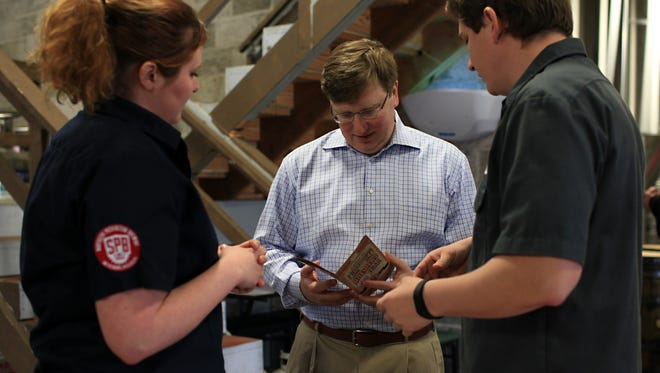Quinby Chunn, owner of Southern Prohibition Brewery, right, takes Lt. Gov. Tate Reeves on a tour of the brewery in downtown Hattiesburg Saturday.