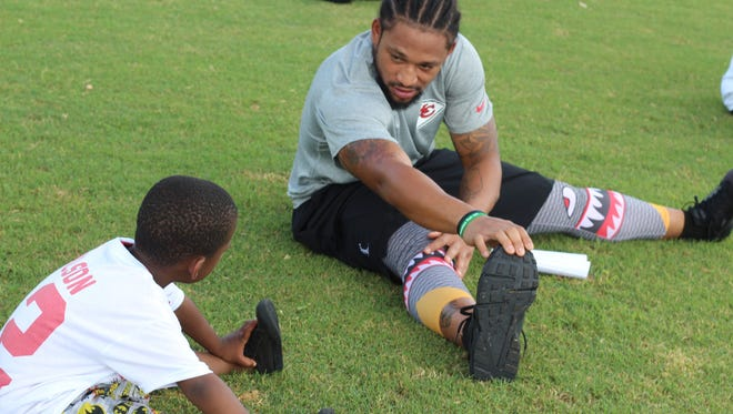 Albert Wilson demonstrates some pre-practice stretching techniques to a local camper.
