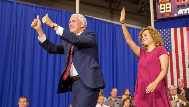 Republican vice presidential candidate, Indiana Gov. Mike Pence and his daughter Charlotte gesture during a campaign stop at the the Rossford Recreation Center in Rossford, Ohio, Friday, Oct. 7, 2016.