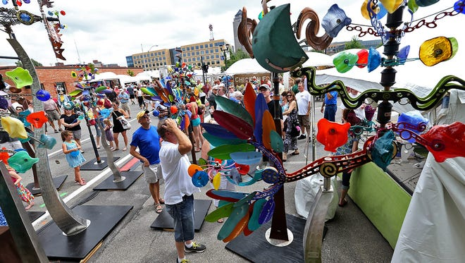 Kinetic sculptures by Andrew Carson drew the attention of the crowd at the Des Moines Arts Festival on June 28, 2014.