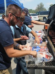 Brandon Lewis prepares to grill free hamburgers for veterans along with other volunteers from Woodsmen of the World at the Welcome Home Veterans event Saturday at Jackson State Community College.