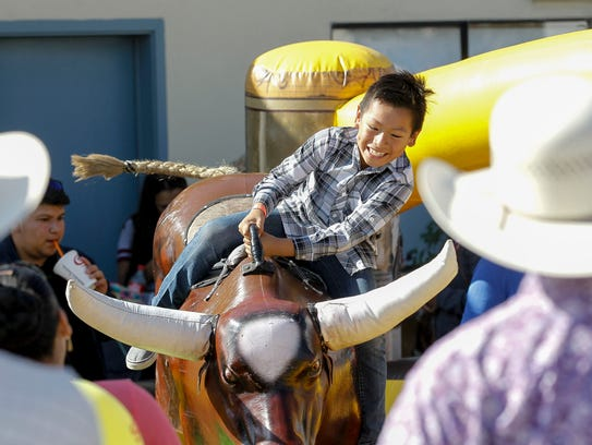 A young boy rides a mechanical bull on East Alisal