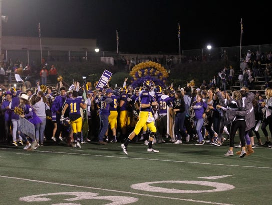 Salinas High students storm the field after the Cowboys