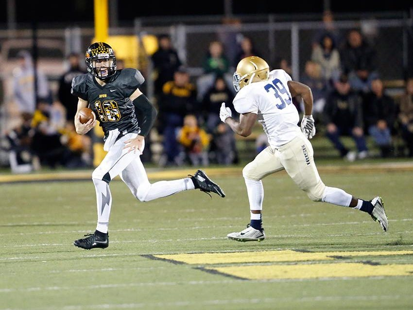 Avon QB Brandon Peters tries to elude Cathedral defender Hugh Davis Friday night in regional action. The Orioles prevailed in double overtime.