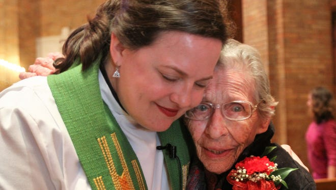 The Rev. Lisa Bates-Froiland hugs Bessie Bray, 100, after a ceremony marking 100 years for Redeemer Lutheran Church at 631 N. 19th St. Bray is believed to be the first to be christened in the church's baptismal font.