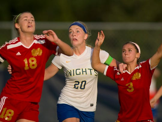 Castle's Katie Schroeder (20) positions herself between Mater Dei defenders Katelyn Zigenfus (18) and Sydney Allison (3) before rising up to head the ball into the net to tie their game at 1-1 at Castle High School Thursday evening. Castle went on to win 4-1.