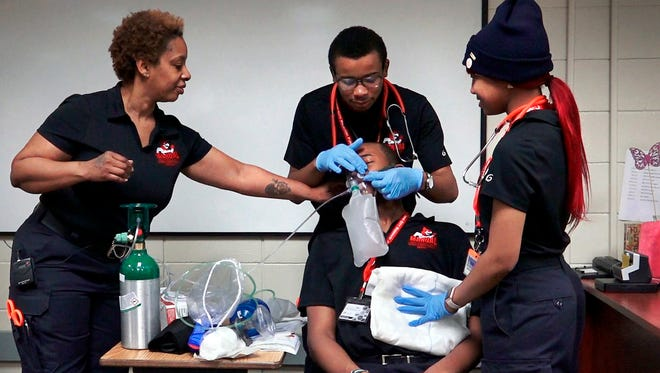 """Under the guidance of Kansas City Fire Department EMT Trina Townsell, high school students Ramon Strickland, standing, center, and Tamia McLaughlin practiced their EMT skills on """"patient"""" Robert Wesley recently at the Manual Career & Technical Center."""