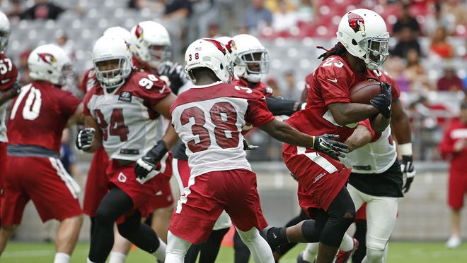 Cardinals' Chris Johnson (23) breaks through some tackles during a drill during the team's first practice at University of Phoenix Stadium on July 29, 2016 in Glendale, Ariz.