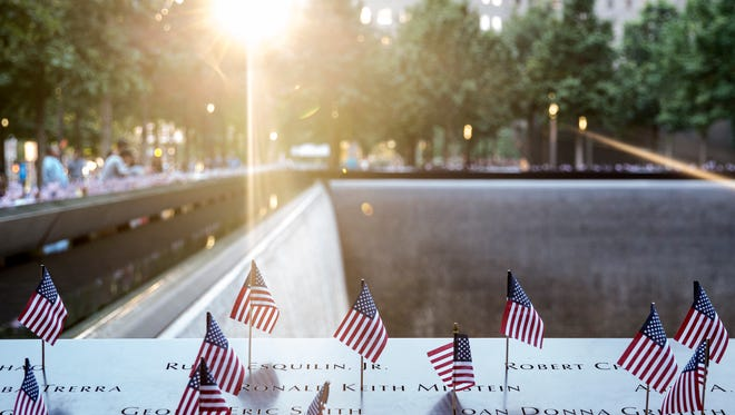 Small American flags are placed in all 2,983 names on the 9/11 Memorial in the Manhattan borough of New York City. The flag placement has become an annual tradition at the site on July 4. (Photo by Alex Wroblewski/Getty Images)