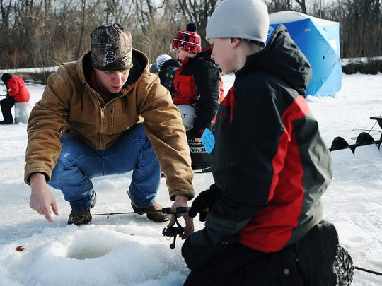 "Reid Jensen, a naturalist intern with the Outdoor Campus, helps Ethan Sheaffer, 11, of Sioux Falls, get set up while ice fishing during a Junior Angler ""Ice Fishing 101"" event in 2015."