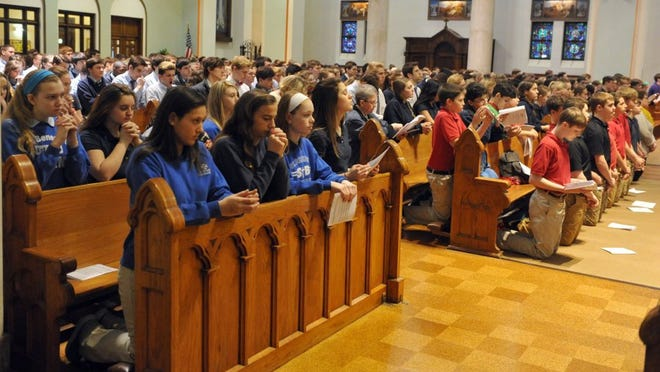 JASON CLARK / COURIER & PRESS   Area Catholic school students kneel down during communion during the Diocese of Evansville National Catholic Schools Week Mass at St. Benedict Cathedral in Evansville Wednesday.