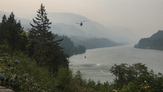 A helicopter takes water from the Columbia River near the Eagle Creek Fire.