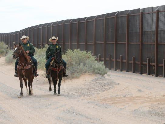 A couple of U.S. Border Patrol agents ride near the