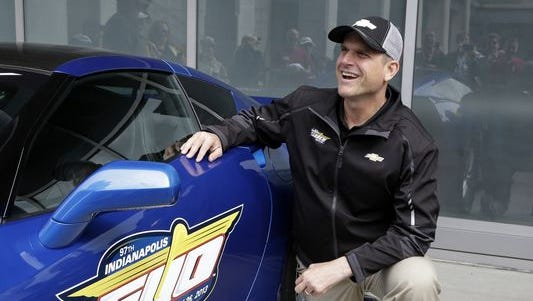Jim Harbaugh poses next to the Chevrolet Corvette Stingray he drove to lead the field for the start of the 2013 Indianapolis 500.