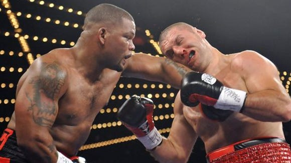 Mike Perez, left, lands a hard left hook on the head of Magomed Abdusalamov during their heavyweight bout in November 2013. Abdusalamov underwent brain surgery after the fight to remove a blood clot from his brain.