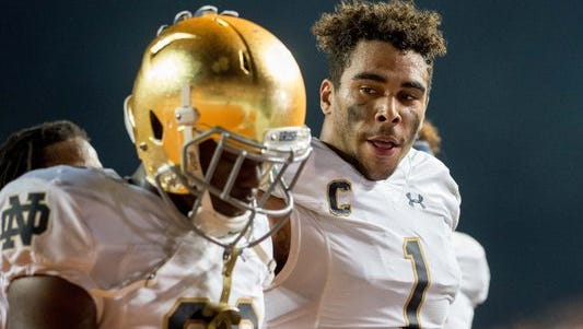 Notre Dame Fighting Irish linebacker James Onwualu (1) consoles cornerback Shaun Crawford (20) as they leave the field after Texas defeated Notre Dame 50-47 in double overtime at Darrell K. Royal-Texas Memorial Stadium Sep 4.